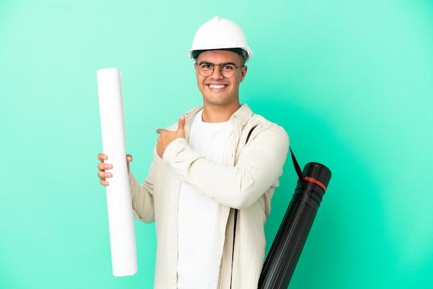 뒤로 가리키는 고립 된 배경 위에 청사진을 들고 젊은 건축가 남자