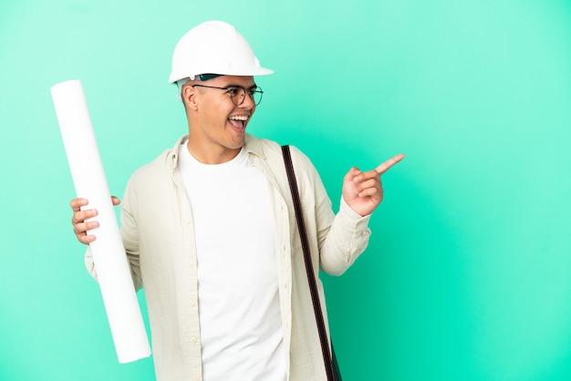 측면에 손가락을 가리키고 제품을 제시하는 격리 된 배경 위에 청사진을 들고 젊은 건축가 남자