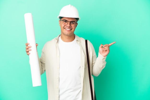 Молодой архитектор мужчина держит чертежи на изолированном фоне, указывая пальцем в сторону