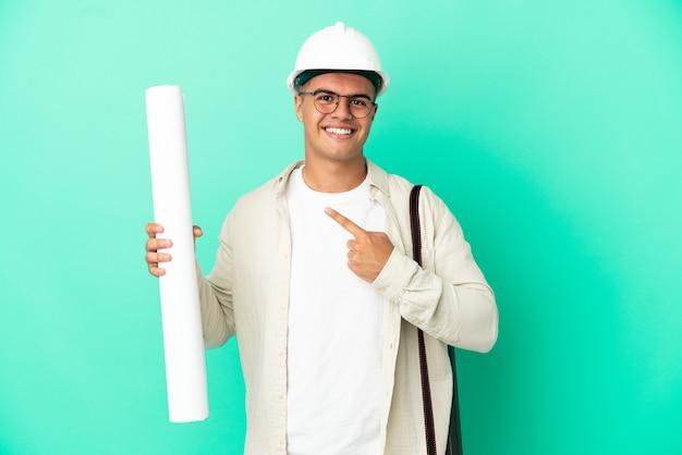 Молодой архитектор мужчина держит чертежи на изолированном фоне, указывая в сторону, чтобы представить продукт