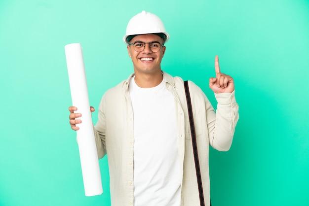 멋진 아이디어를 가리키는 외진 배경 위에 청사진을 들고 있는 젊은 건축가