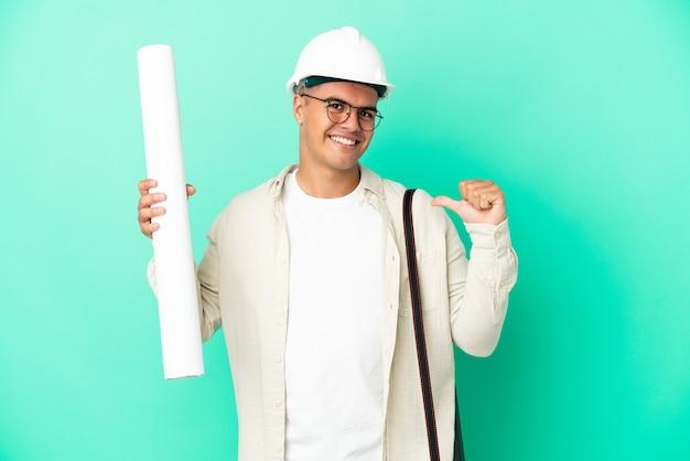 Молодой архитектор мужчина держит чертежи на изолированном фоне, гордый и самодовольный