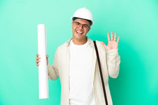 Молодой архитектор мужчина держит чертежи на изолированном фоне, салютуя рукой с счастливым выражением лица