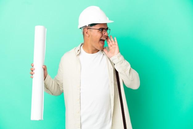 Молодой архитектор мужчина держит чертежи на изолированном фоне и кричит с широко открытым ртом в сторону