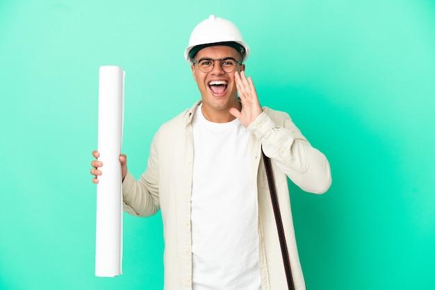 입 벌리고 외치는 격리 된 배경 위에 청사진을 들고 젊은 건축가 남자