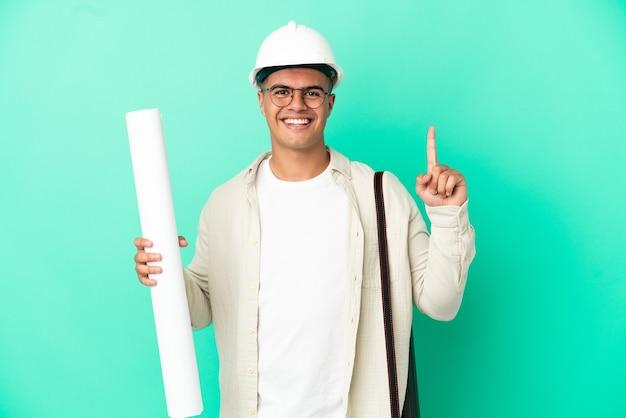 Молодой архитектор мужчина держит чертежи на изолированном фоне, показывая и поднимая палец в знак лучших