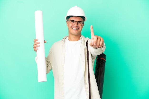 Молодой архитектор мужчина держит чертежи на изолированном фоне, показывая и поднимая палец