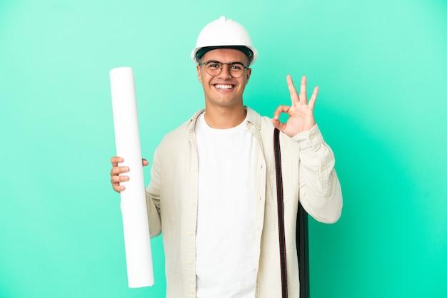 손가락으로 확인 표시를 보여주는 고립 된 배경 위에 청사진을 들고 젊은 건축가 남자