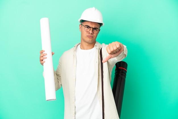 부정적인 표현으로 아래로 엄지 손가락을 보여주는 격리 된 배경 위에 청사진을 들고 젊은 건축가 남자