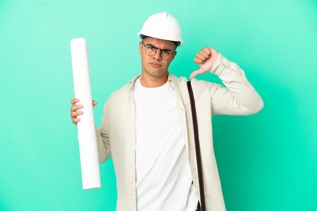 Молодой архитектор мужчина держит чертежи на изолированном фоне, показывая большой палец вниз с негативным выражением лица