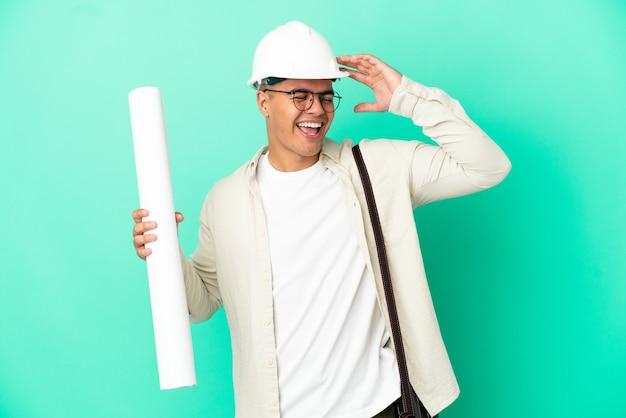 Молодой архитектор мужчина держит чертежи на изолированном фоне, много улыбаясь