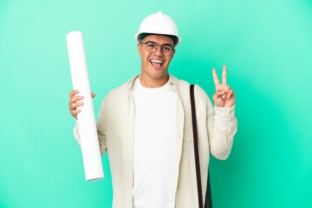 Молодой архитектор мужчина держит чертежи на изолированном фоне улыбается и показывает знак победы