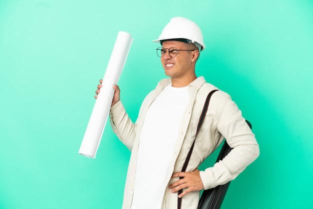 외진 배경 위에 청사진을 들고 있는 젊은 건축가 남자는 노력을 해서 요통으로 고통받고 있다