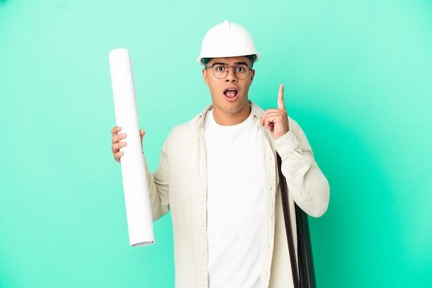 Молодой архитектор мужчина держит чертежи на изолированном фоне, думая об идее, указывая пальцем вверх