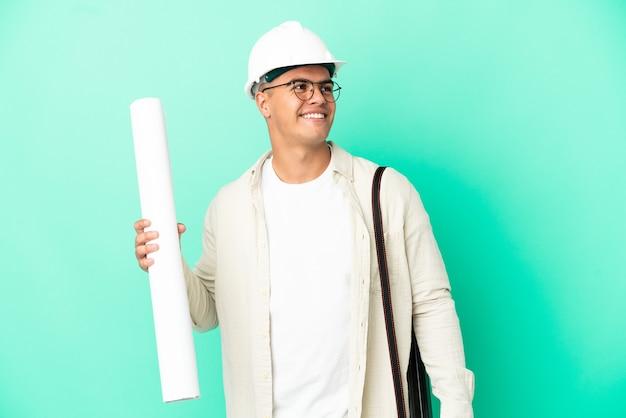 외진 배경 위에 청사진을 들고 올려다보는 동안 아이디어를 생각하는 젊은 건축가