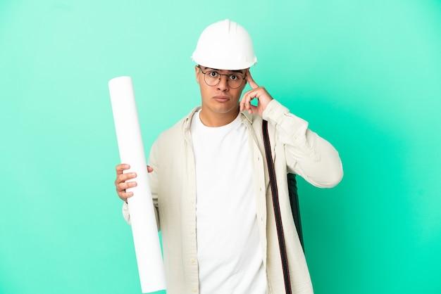 아이디어를 생각하는 격리 된 배경 위에 청사진을 들고 젊은 건축가 남자