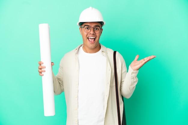 충격 된 표정으로 격리 된 배경 위에 청사진을 들고 젊은 건축가 남자