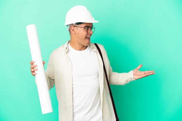 Молодой архитектор мужчина держит чертежи на изолированном фоне с удивленным выражением лица, глядя в сторону