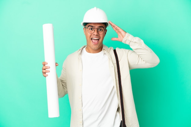 Молодой архитектор мужчина держит чертежи на изолированном фоне с удивленным выражением лица
