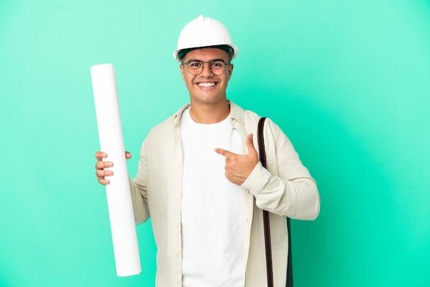 놀라운 표정으로 격리 된 배경 위에 청사진을 들고 젊은 건축가 남자