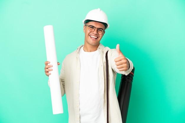 何か良いことが起こったので、親指を立てて孤立した背景の上に青写真を保持している若い建築家の男