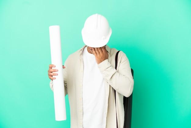 Молодой архитектор мужчина держит чертежи на изолированном фоне с усталым и больным выражением лица