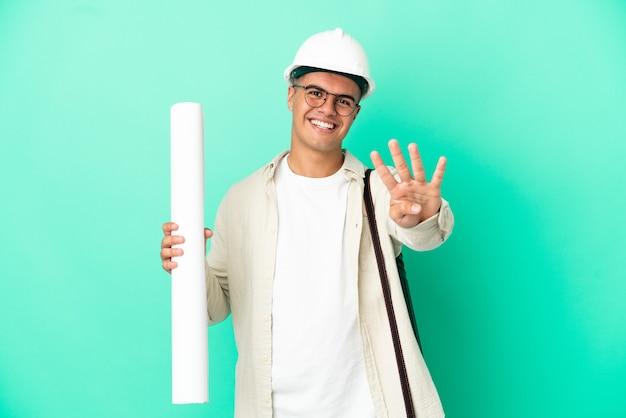 외진 벽에 청사진을 들고 행복하고 손가락으로 4를 세는 젊은 건축가