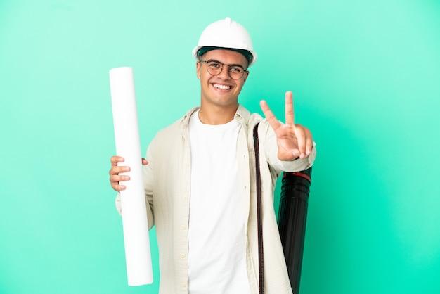 외진 벽에 청사진을 들고 웃고 있는 젊은 건축가 남자