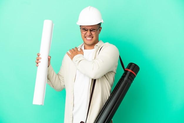 외진 벽에 청사진을 들고 있는 젊은 건축가는 노력을 했다는 이유로 어깨 통증으로 고통받고 있다