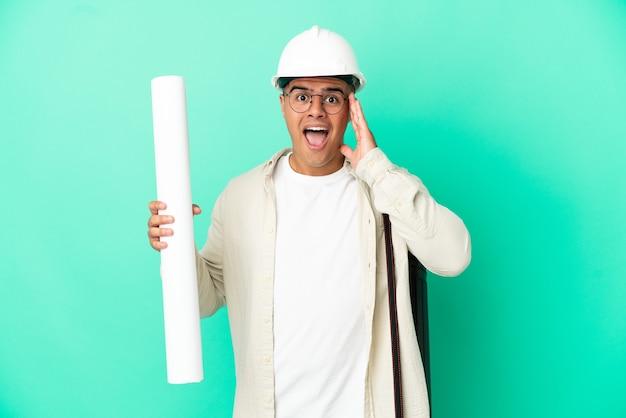 놀라움과 놀란 표정으로 외진 벽에 청사진을 들고 있는 젊은 건축가