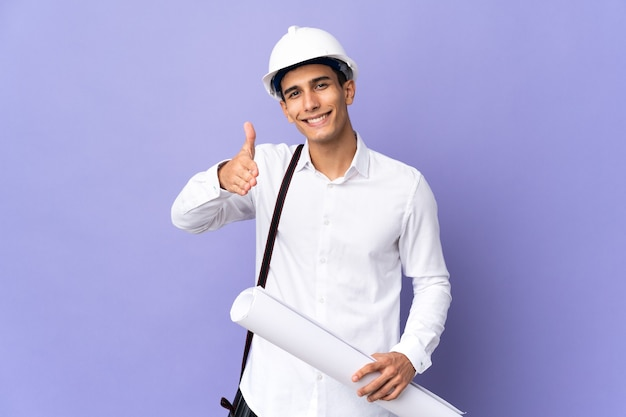 Young architect man isolated on background shaking hands for closing a good deal