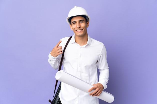 Молодой архитектор человек изолирован на фоне, показывая большой палец вверх жест