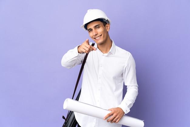 행복 한 표정으로 앞을 가리키는 배경에 고립 된 젊은 건축가 남자