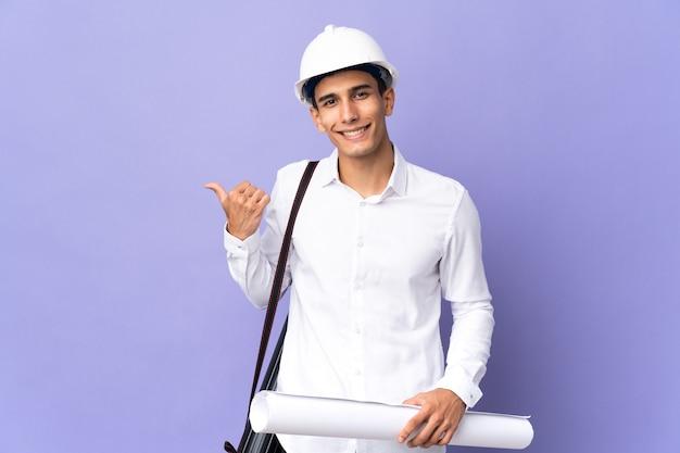 Молодой архитектор человек изолирован на фоне, указывая в сторону, чтобы представить продукт Premium Фотографии