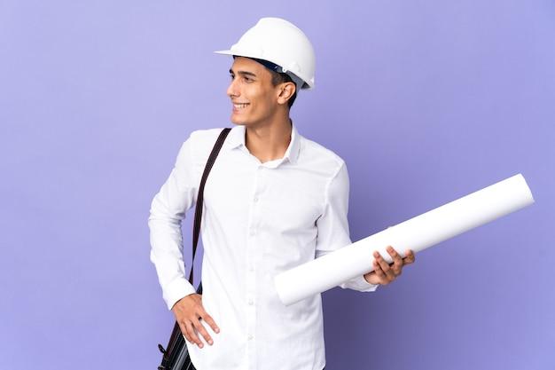 엉덩이에 팔을 포즈와 미소 배경에 고립 된 젊은 건축가 남자