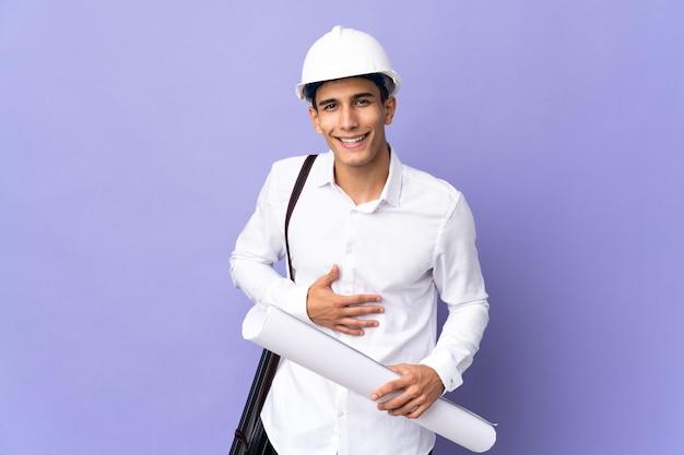Молодой архитектор человек изолирован на фоне много улыбаясь