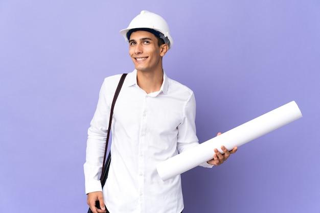 Молодой архитектор человек изолирован на фоне, думая об идее, глядя вверх