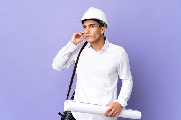 좌절과 귀를 덮고 벽에 고립 된 젊은 건축가 남자