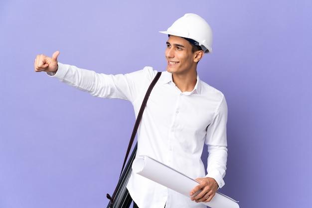 제스처를 엄지 손가락을주는 벽에 고립 된 젊은 건축가 남자