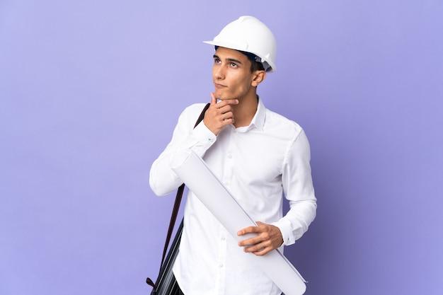 의심을 가지고 벽에 고립 된 젊은 건축가 남자