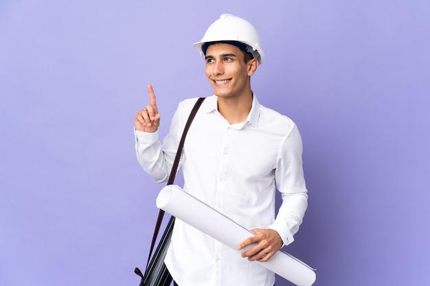 좋은 아이디어를 가리키는 벽에 고립 된 젊은 건축가 남자