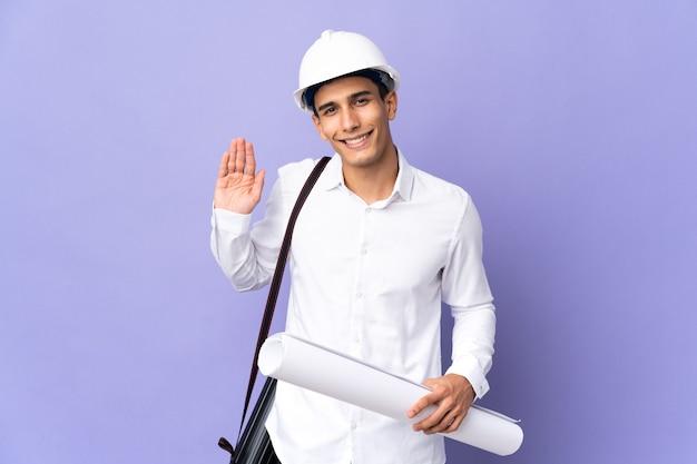 幸せな表情で手で敬礼する壁に孤立した若い建築家の男