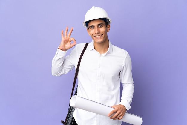 손가락으로 ok 사인을 보여주는 벽에 고립 된 젊은 건축가 남자