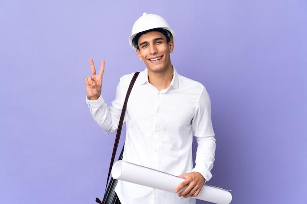 웃 고 승리 기호를 보여주는 벽에 고립 된 젊은 건축가 남자