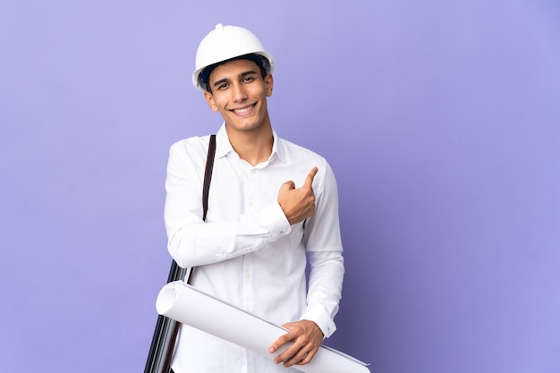Young architect man isolated on wall pointing back