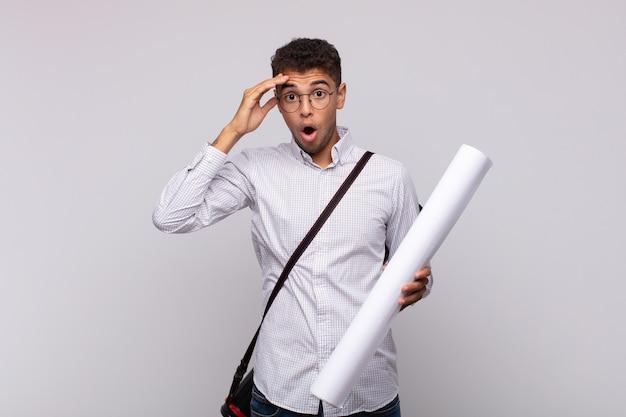 幸せに見え、驚き、驚き、笑顔で、驚くべき信じられないほどの良いニュースを実現している若い建築家の男