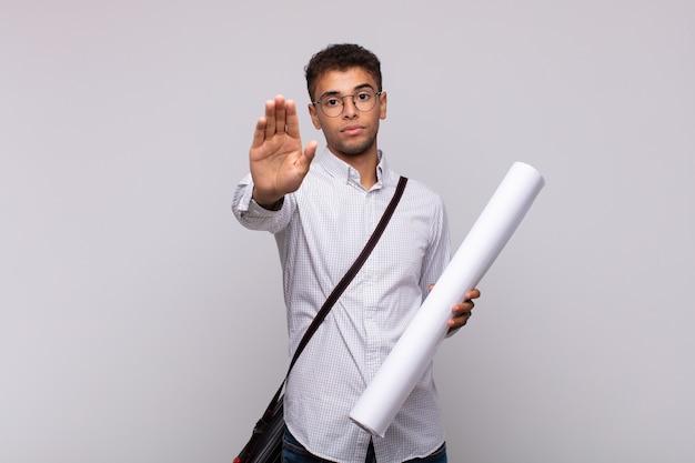 Молодой архитектор выглядит серьезным, суровым, недовольным и злым, показывая открытую ладонь, делая стоп-жест