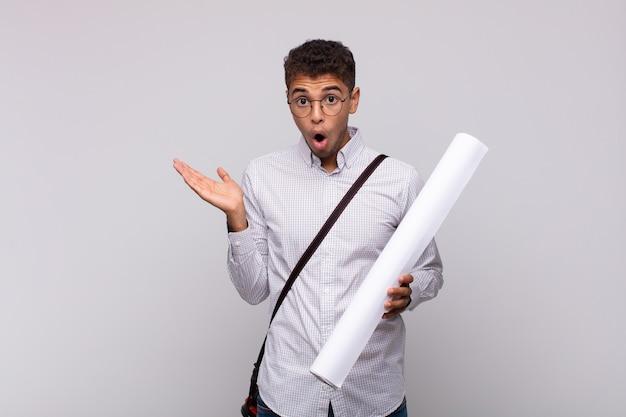 Молодой архитектор выглядит удивленным и шокированным, с отвисшей челюстью держит объект открытой рукой сбоку