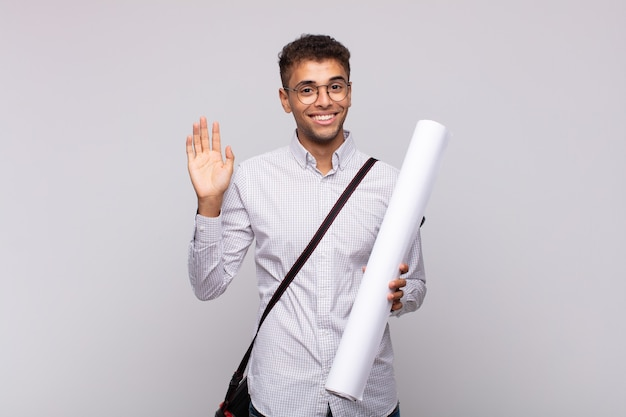 Young architect man smiling happily and cheerfully, waving hand, welcoming and greeting you, or saying goodbye