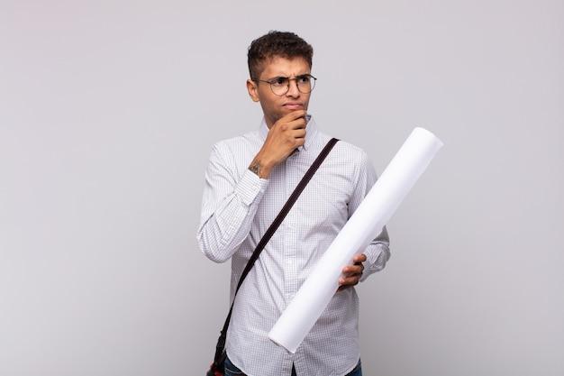 Молодой архитектор человек думает, чувствует себя сомневающимся и сбитым с толку, с разными вариантами, задаваясь вопросом, какое решение принять
